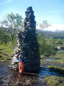 Girl in front of big cairn