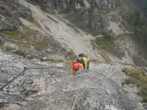 Mutter und Tochter am Seil gesichert auf steilem Klettersteig unterwegs