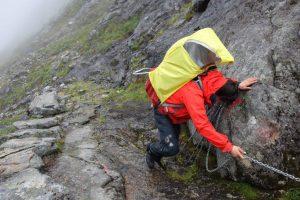 Steiler und nasser Abstieg an einer Kette über rutischige Felsplatten, mit Kraxe auf dem Rücken
