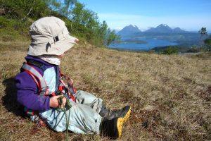 Kind mit Klettergurt genießt die Aussicht auf Berge und Meer