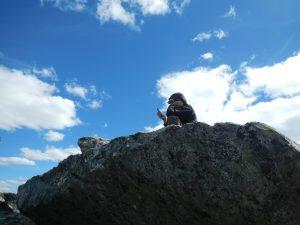 Interaktion eines Wanderers auf einem Stein mit einem Handy