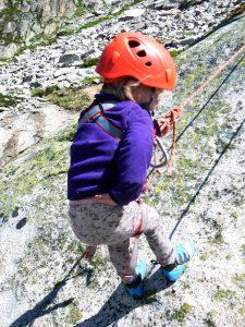 Kleinkind wird nach dem Klettern am Fels abgelassen