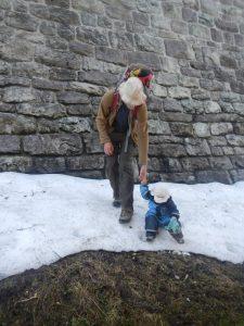 Kind sitzt im Schnee, findet das offenbar lustiger als Laufen