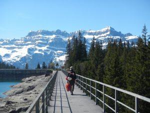 Frau mit Kletterausrüstung geht über Staudamm in Richtung auf schneebedeckte Berge