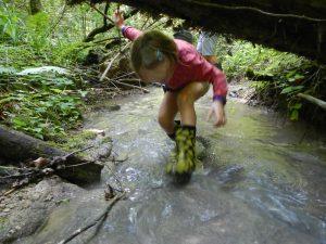 Mädchen duckt sich unter einem Baumstamm hindurch beim Laufen durch einen Bach