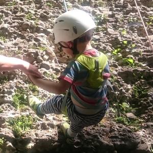 Kind schwingt am Fels, mit Klettergurt und Helm und Seil