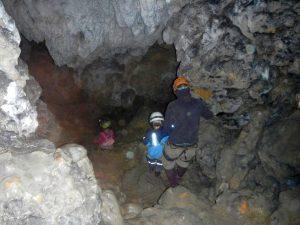 Kleine Kinder ausgerüstet mit Helmen und Stirnlampen sitzen in einer Höhle