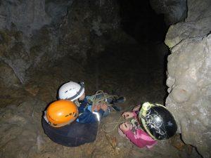 Kinder und Mutter mit Helm und Stirnlampen sitzen in einer Höhle