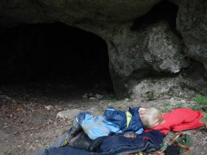 Erschöpftes Kind liegt vor dem Höhleneingang