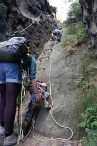 Kinder klettern einen Klettersteig in der sächsischen Schweiz empor, mit loser Seilsicherung