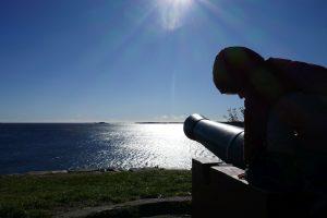 Kletter-Kind auf alter Kanone mit Sicht aus Meer