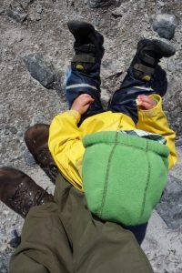 Kleinkind mit Wanderschuhen, dass sich an Papas Schuhen für eine Pause anlehnt
