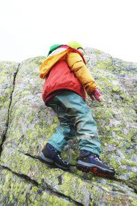 Kind beim Klettern auf Felsen