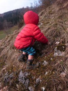 Kind kraxelt über eine steile Wiese