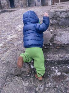 Kleinkind krabbelt eine alte Steintreppe hoch