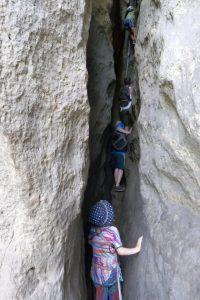 Kinder im Felsspalt, durch den eine Stiege führt