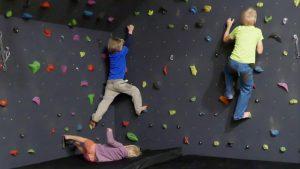 Kinder unterwegs an einer vorgefertigten Indoor-Kletterwand