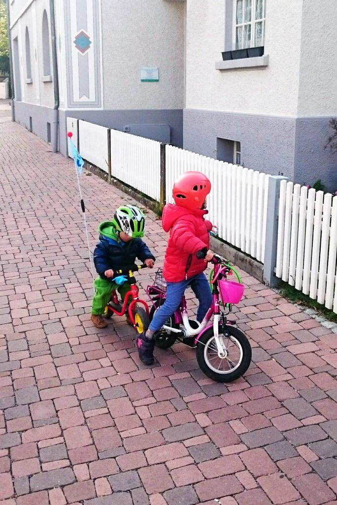 Ein Rowdy-Laufrad-Fahrer bedrängt die Kinderfahrrad-Fahrerin